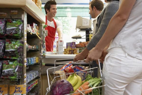 Buying Groceries In Line Supermarket Getty