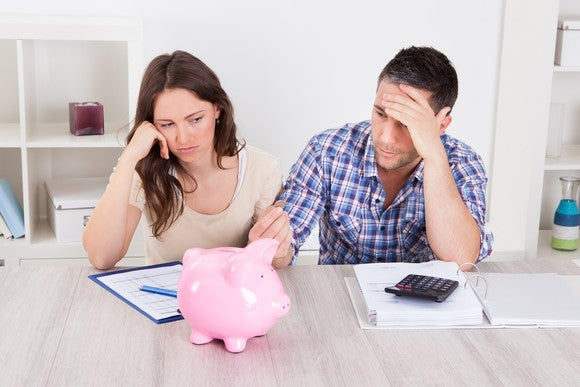 Couple Frustrated With Retirement Saving Piggy Bank Getty