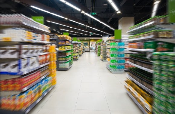 A view down a super market aisle shows rows of various food items on either side