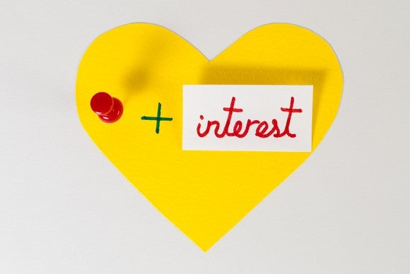 "A yellow paper heart containing a pin and the word ""interest."""