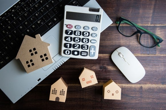 A calculator, glasses, and a computer, with wood cutouts of houses, on a desk