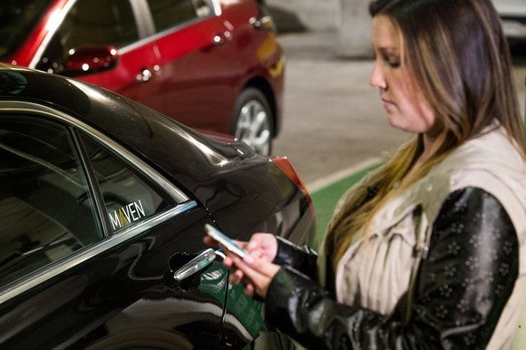 Woman using smartphone and holding keys, standing next to a car with a sticker in the window that says Maven.