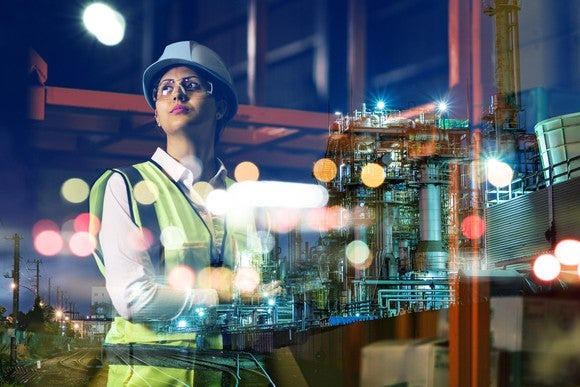 Woman wearing hardhat in industrial setting