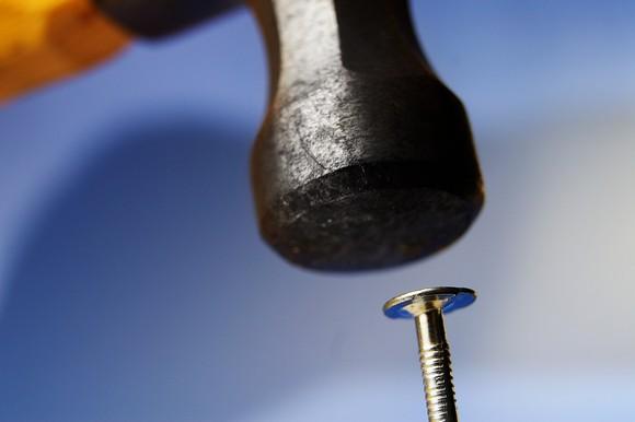 A hammer hitting a nail.