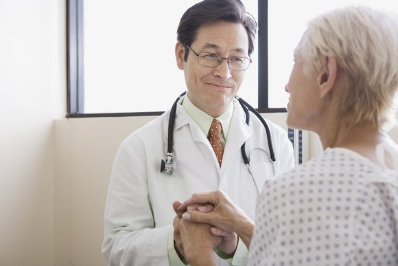 Doctor Holding Patient Hand And Smiling Getty