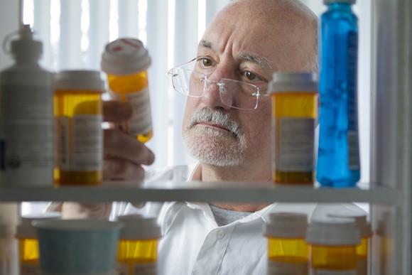 Senior Looking At Prescripton Drugs In Medicine Cabinet Getty