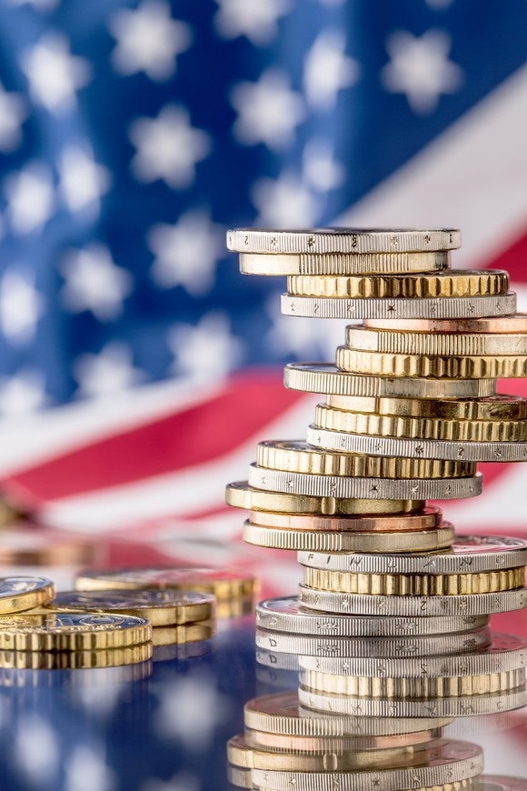 coins piled in front of an Amerian flag