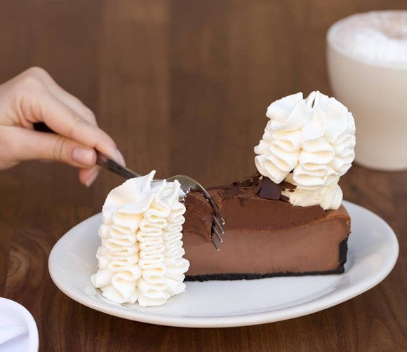 A person digging into a slice of pie from the Cheesecake Factory.