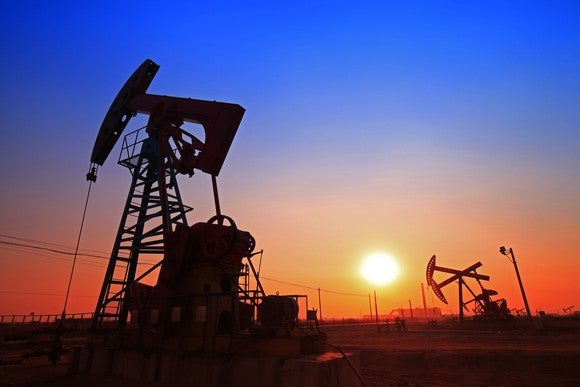 Oil pump on a field at sunset.