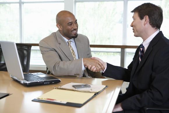 Two Businessmen Shaking Hands Laptop Boardroom Getty