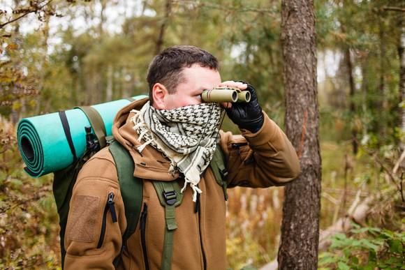 Survivalist in the outdoors looking through binoculars.