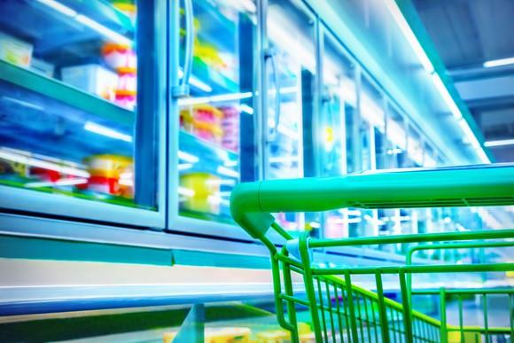 Green shopping cart in frozen foods aisle