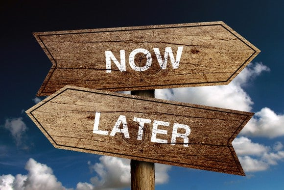 "Signs pointing in opposite directions saying ""NOW"" and ""LATER"""