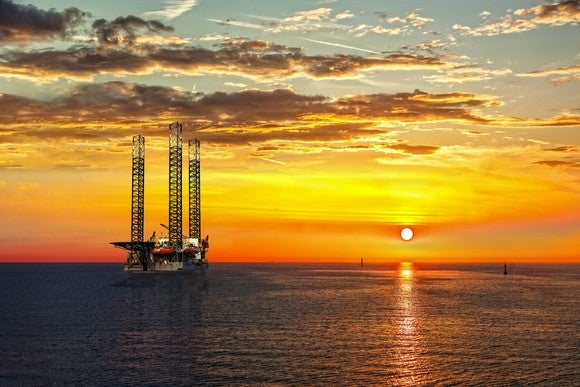 An oil rig in the ocean at sunset