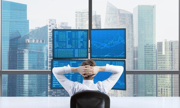 Investor Looking At Charts And Data Overlookin A Skyline Gettyimages