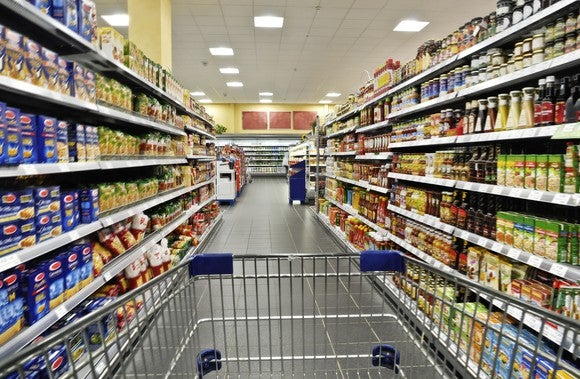 Grocery store aisle with shopping cart.