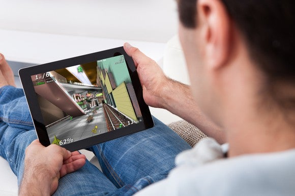 A man playing a video game on a tablet computer.