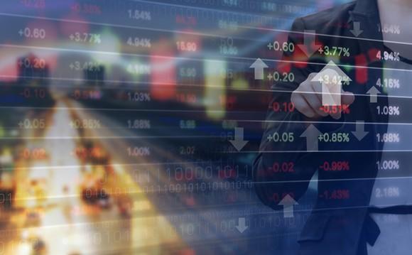A businessman points to an upward-facing arrow on a financial chart.