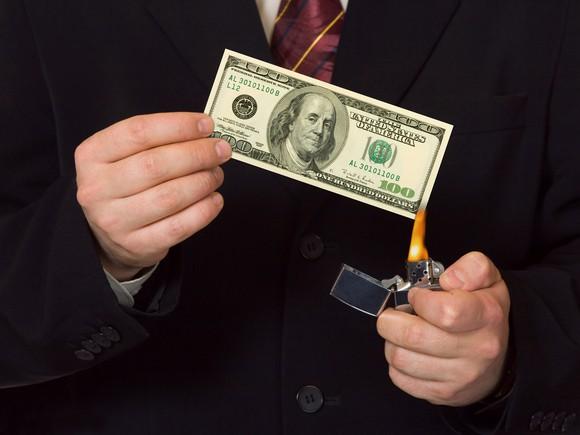 Getty Man Burning The Money