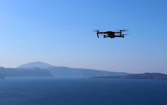 Drone flying over ocean with mountains in the background