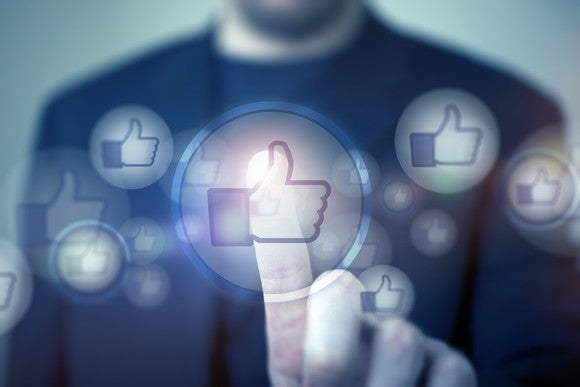 """A man pressing Facebook's thumbs-up """"like"""" symbol."""