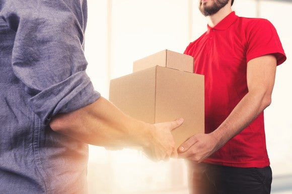 Man in purple shirt delivering boxes to man in red shirt.
