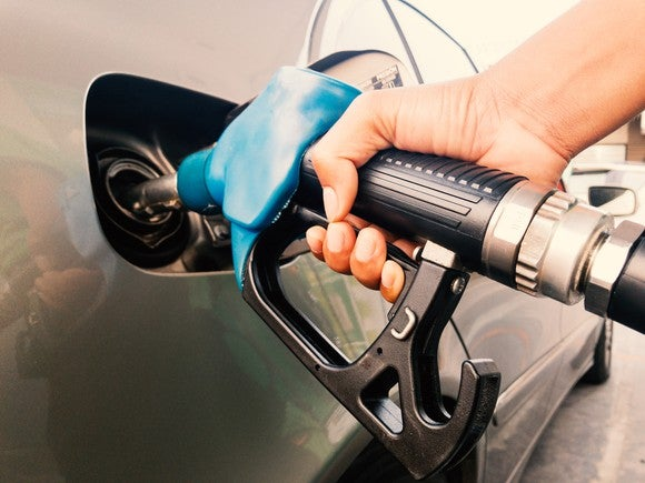 A hand pumping gas into a car.