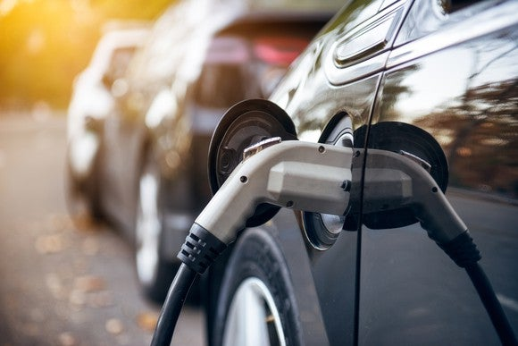 A close-up shot of a an electric car plugged in.