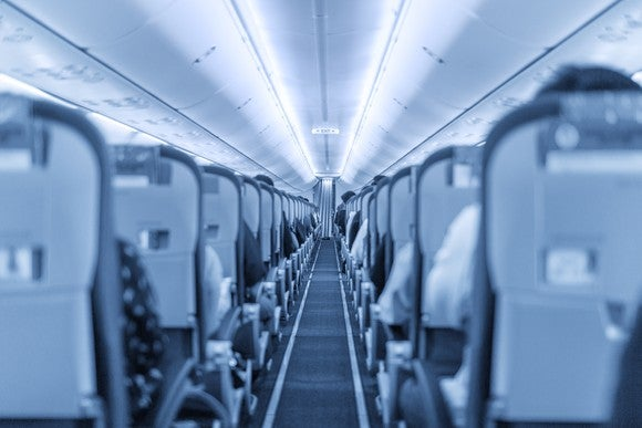 Looking down the interior aisle of a plane, with seats on either side