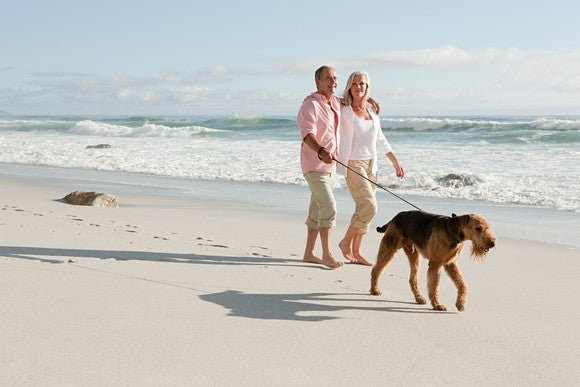 Older couple walking on beach with dog.