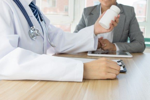 Doctor And Patient With Drug Bottle Getty