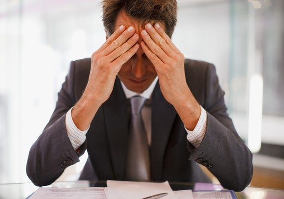 A frustrated businessman sits with his head in his hands.