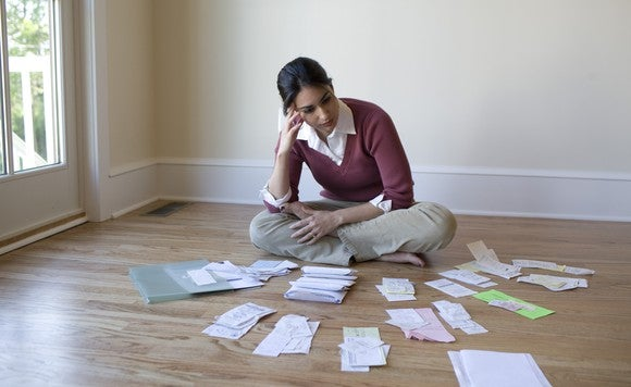 Woman with a worried look sitting on the floor, looking through piles of receipts.