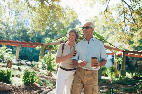 Senior man and woman walking in nature.