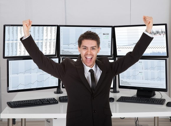 Stock broker celebrating in front of multiple computer screens.