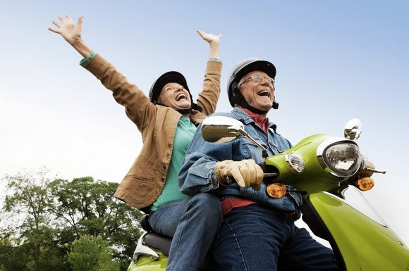 Retired couple riding on a scooter.