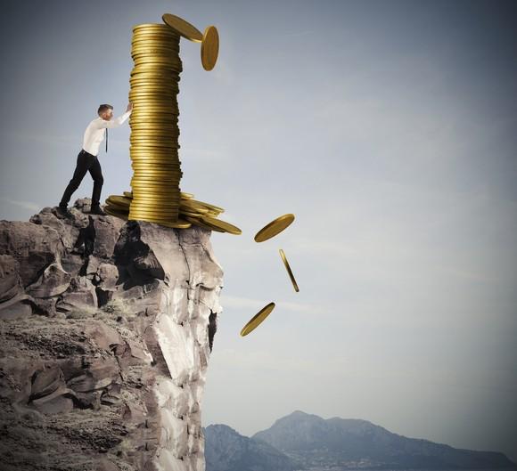 Man pushing money off a cliff