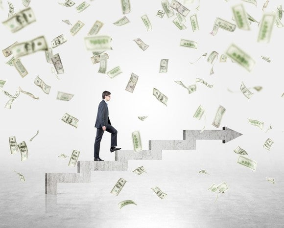 Businessman climbing steps while it rains money