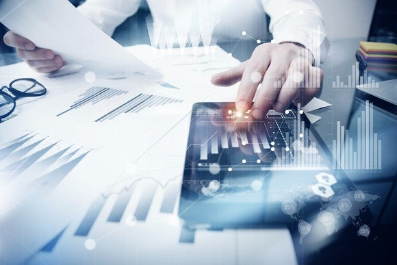 An investor looks over a paper and tablet with financial results.