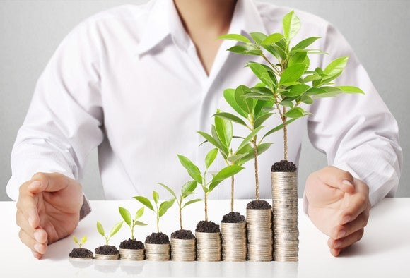 Man with progressively higher stacks of coins in front of him, with green sprouts growing out of them.