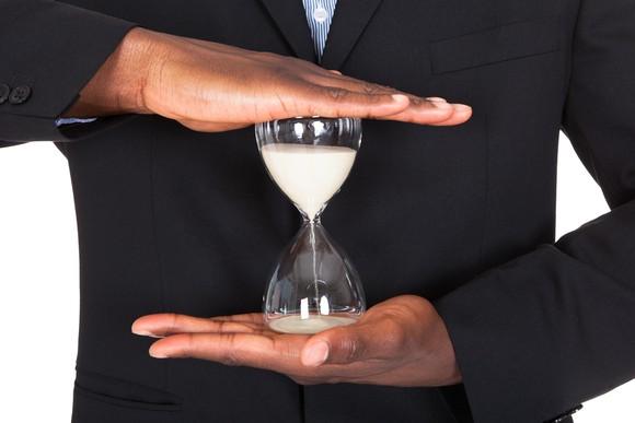 An hourglass held between two hands.