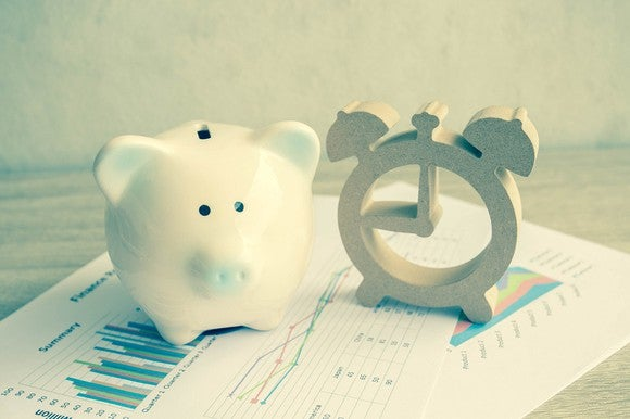 A piggy bank and an alarm clock sitting on top of pages of financial data.