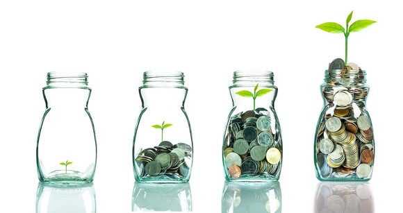 Four glass jars, each filled progressively higher with coins and a green sprout.