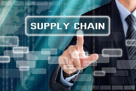 Man pointing to screen with words Supply Chain on it.