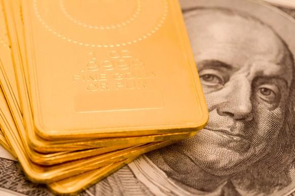 Gold ingots sitting on top of money.