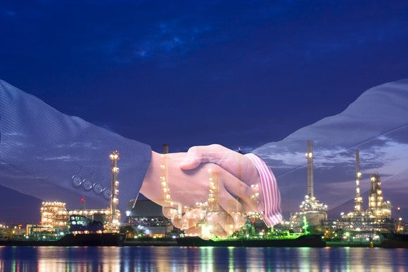 Double exposure of handshake and refinery plant.