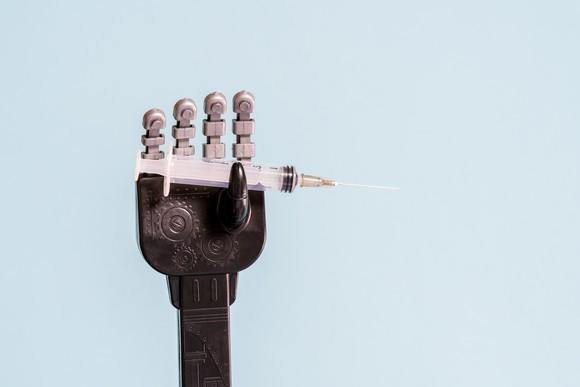 Robot hand holding a syringe