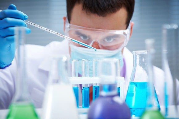 Chemist in lab with test tubes.