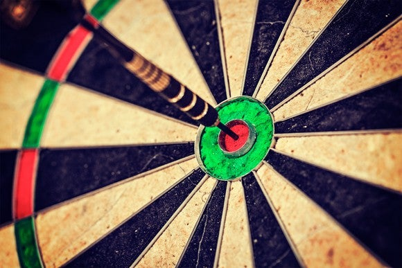 A single dart hitting the bull's-eye of a dart board.
