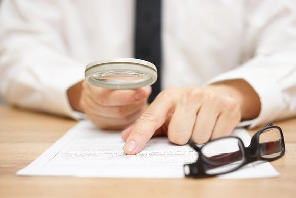 A hand holding a magnifying glass over a piece of paper, next to a folded pair of glasses.